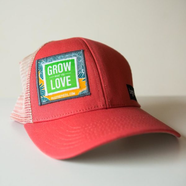 "a salmon colored hat with ""grow what you love"" embroidered on the face"